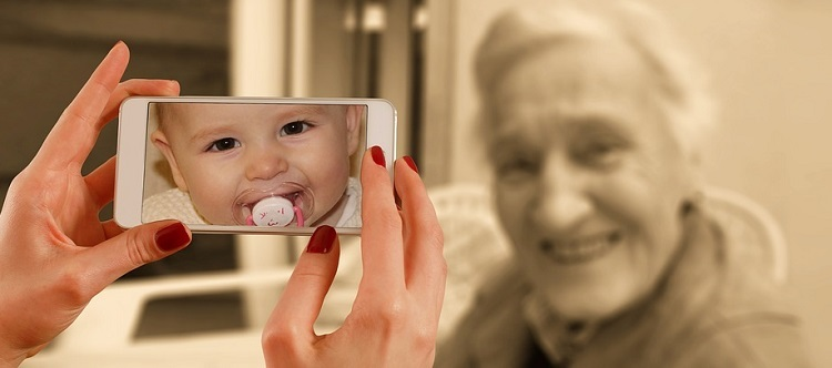 Image of baby in mobile device in front of aged-woman