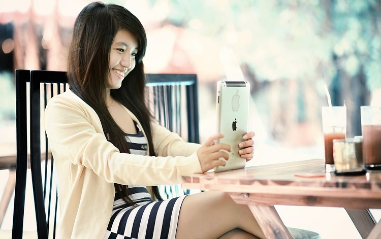 Girl smiling using an iPad
