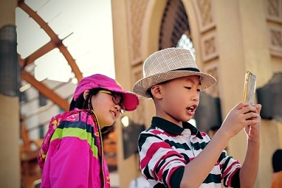 Two young children using a smart phone