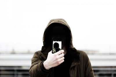 Person in a hoodie taking a picture of themself