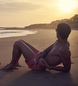 Shirtless man posing on the beach
