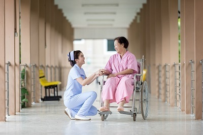 Person caring for woman in a wheelchair