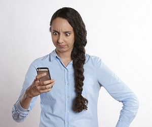 Woman staring at phone, surprised