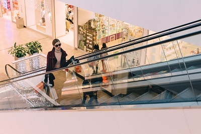 Woman riding mall escalator with full shopping bags