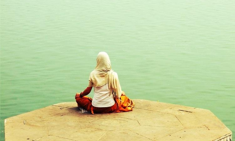 Woman meditating near the water