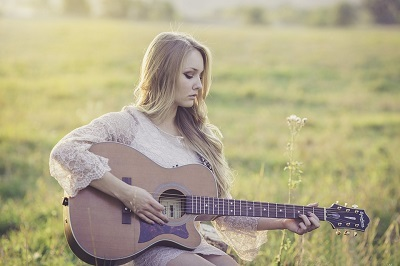 Woman playing a guitar in a field