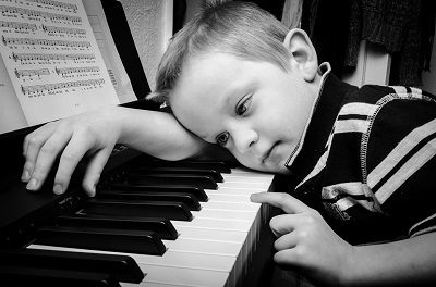 Young boy sleeping over a piano