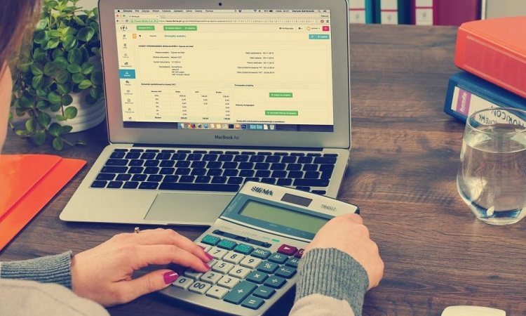 Expense reports on a laptop and a calculator