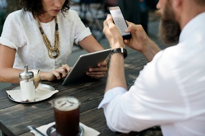 People submitting expenses on a smartphone at a coffee shop